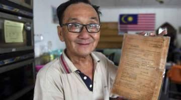 DISIMPAN RAPI: Tan Yong Min, 61, atau lebih mesra dengan panggilan 'Ameng' menunjukkan lesen perniagaan berusia 65 tahun di kedainya iaitu Kopitiam Kampung Parit, Negeri Sembilan. — Gambar Bernama