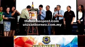 DILANCAR: Joseph melancarkan Buku Koleksi Artikel Kolokium Penyelidikan SMK Batu Kawa sambil disaksikan oleh pasukan pentadbiran sekolah SMK Batu Kawa di Kuching pada 4 Ogos lalu.