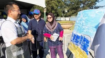 AZHAR (kiri) sedang memerhati hasil salah seorang peserta pertandingan mewarna kemerdekaan.