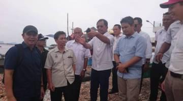 JAUJAN (tiga kiri) bersama Ginun (dua kiri) dan Nazri (empat kiri) meninjau tapak pembinaan pasar ikan sementara di sini pada Sabtu.