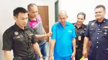 ALBANI (tengah) diiringi pegawai penjara keluar dari Mahkamah Sesyen selepas selesai prosiding.