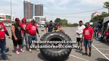 ANGKAT TAYAR: Salah seorang peserta berusaha untuk mengangkat tayar dalam acara Tyre Flip.