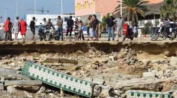 RUNTUH: Orang ramai berkumpul di tapak jambatan runtuh selepas banjir kilat di bandar Bir Challouf, Tunisia. — Gambar AFP