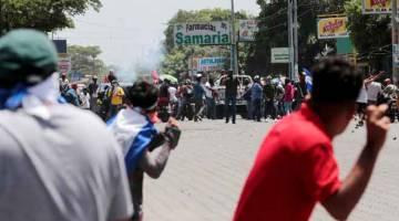 KACAU-BILAU: Penunjuk perasaan melontar batu ketika bertempur dengan penyokong Ortega                    di Managua, Nicaragua kelmarin. — Gambar Reuters