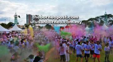 MERIAH: Para peserta menghamburkan serbuk berwarna-warni ke udara sebelum acara larian bermula.