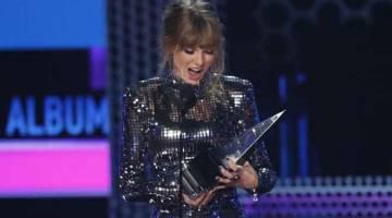 MENANG BESAR: Taylor Swift melihat trofi 'Album - Pop/Rock' yang dimenanginya semasa Anugerah Muzik Amerika 2018 di Los Angeles, California baru-baru ini. — Gambar Reuters