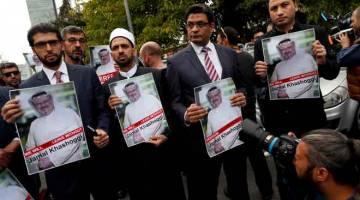 BEBAS KHASHOGGI!: Aktivis hak asasi dan rakan Khashoggi memegang gambar beliau ketika demonstrasi di luar Konsulat Arab Saudi di Istanbul, Turki pada 8 Oktober lalu. — Gambar Reuters