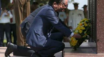 BERI PENGHORMATAN: Abe dan Morrison meletak kalungan bunga di tugu peringatan perang, Darwin Cenotaph, di Darwin, Australia semalam. — Gambar AFP