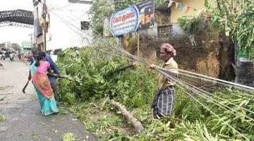 ANGKARA GAJA: Penduduk India mengalih pokok tumbang berhampiran stesen kereta api di Nagapattinam dalam negeri                         Tamil Nadu, selatan India, semalam selepas Siklon Gaja melanda wilayah tersebut. — Gambar AFP