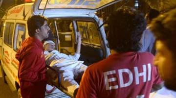 MANGSA LETUPAN: Dalam gambar yang diambil kelmarin, pekerja ambulans sukarelawan Pakistan membawa seorang mangsa letupan yang cedera ke hospital di Karachi. — Gambar AFP