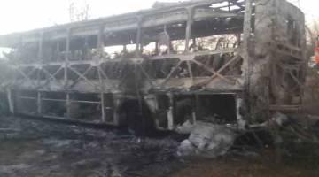 TINGGAL RANGKA: Bangkai bas penumpang yang rentung selepas ia terbakar kelihatan di Beitbridge, Zimbabwe dalam gambar serahan yang diterima kelmarin. — Gambar Reuters
