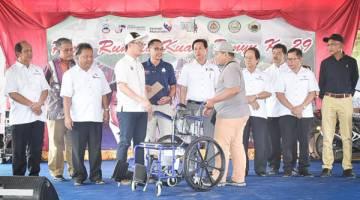 JUNZ (empat dari kiri) menyampaikan kerusi roda kepada salah seorang wakil penerima.