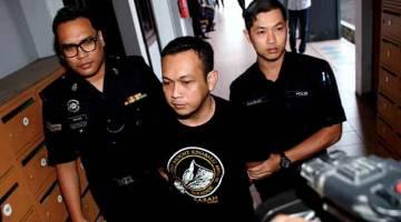 DIBICARAKAN: Megat Khairul (tengah) diiringi anggota polis selepas mengaku tidak bersalah di Mahkamah Sesyen Ipoh semalam atas dua pertuduhan meminta dan menerima suapan sebanyak RM3,000 daripada seorang lelaki, dua tahun lepas. — Gambar Bernama