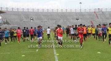 UJIAN: Pemain-pemain memanaskan badan pada sesi ujian hari pertama pemilihan pemain-pemain Sarawak di Stadium Negeri, Petra Jaya semalam.