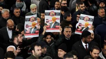 TURUT BERSIMPATI: Orang ramai yang membawa gambar Khashoggi menghadiri acara pengebumian simbolik untuk Khashoggi di Masjid Fatih di Istanbul, Turki, pada 16 November lepas. — Gambar Reuters