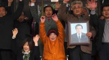 TERIMA PAMPASAN: Kim Sung-joo (duduk tengah), mangsa buruh paksaan tentera Jepun sewaktu penjajahannya di semenanjung Korea dari 1910 hingga 1945, dan saudara-mara mangsa lain             menunjukkan reaksi selepas keputusan dibaca di Mahkamah Agung di Seoul semalam. — Gambar AFP