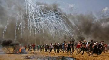 HURU-HARA: Penduduk Palestin mencari perlindungan daripada gas pemedih mata sewaktu pertelingkahan dengan pasukan                 keselamatan Israel dekat sempadan antara Israel dan Semenanjung Gaza, ke timur Jabalia pada 14 Mei lepas, ketika penduduk Palestin membantah perasmian kedutaan Amerika Syarikat yang kontroversi selepas ia dipindahkan ke Baitulmuqaddis. — Gambar AFP