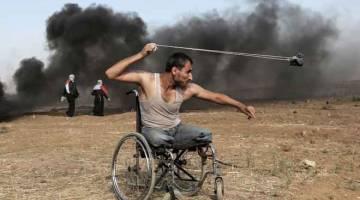 BERSEMANGAT WAJA: Penduduk Palestin berusia 29 tahun, Saber al-Ashkar, melontar batu sewaktu pertelingkahan dengan tentera Israel di sepanjang sempadan dengan semenanjung Gaza, ke timur Kota Gaza, pada 11 Mei lepas, ketika penduduk Palestin berdemonstrasi bagi menuntut hak untuk kembali ke tanah air mereka yang bersejarah di bumi yang kini dikenali sebagai Israel. — Gambar AFP