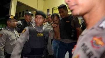 DITANGKAP SEMULA: Polis mengiringi seorang banduan                                                                       yang ditangkap semula                        selepas dia meloloskan diri dari penjara di Banda Aceh, wilayah Aceh, kelmarin. — Gambar AFP