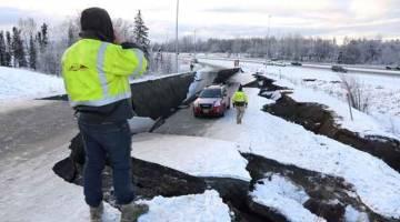 TERKANDAS: Sebuah kenderaan terkandas dalam runtuhan jalan raya berdekatan lapangan terbang selepas gempa bumi melanda di Anchorage, Alaska di Amerika Syarikat kelmarin. — Gambar Reuters