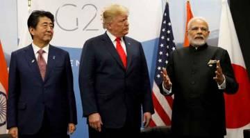 KUKUHKAN HUBUNGAN: Trump (tengah) berjumpa dengan Abe (kiri) dan Modi semasa persidangan G20 bagi kuasa ekonomi di Buenos Aires, Argentina kelmarin. — Gambar Reuters