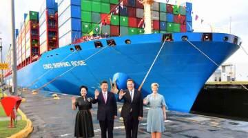 TINGKAT KERJASAMA: Xi (dua kiri) dan Varela melambai ke arah wartawan sambil diapit oleh isteri masing-masing Peng Liyuan (kiri) dan Lorena Castillo (kanan) di hadapan kapal kontena Chinese Cosco Shipping Rose di Cocoli yang baharu dirasmikan di Terusan Panama pada 3 Disember lepas. — Gambar AFP