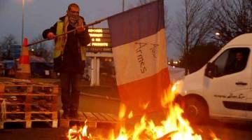 TUNJUK MARAH: Seorang penunjuk perasaan yang memakai ves kuning, simbol protes pemandu Perancis yang menentang kenaikan harga diesel, membawa bendera dekat puing terbakar di jalan menuju ke A2 Paris-Brussels Motorway, di Fontaine-Notre-Dame, Perancis, kelmarin. — Gambar Reuters
