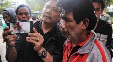 DIBUNUH KEJAM: Gambar ini yang diambil kelmarin menunjukkan anggota keluarga mangsa pembunuhan di Nduga mempamerkan gambar dalam telefon pintar mereka yang menunjukkan salah seorang mangsa, di Wamena, wilayah Papua. — Gambar AFP
