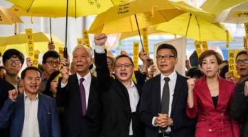 AKTIVIS PRODEMOKRASI: Dalam gambar yang diambil pada 19 November 2018,  Chu (dua kiri), Tai (tengah) dan Chan (dua kanan) serta aktivis prodemokrasi lain melaungkan slogan sebelum mereka memasuki Mahkamah Majistret Kowloon Barat di Hong Kong. — Gambar AFP