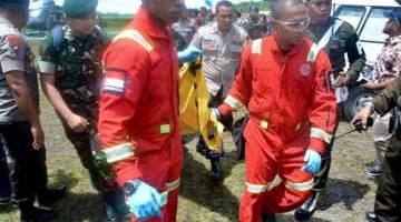 DIBAWA PULANG: Mayat pekerja pembinaan, dibunuh oleh kumpulan pemisah, dilihat diusung dari helikopter tentera di Lapangan Terbang Mozes Kilangin Timika di Papua semalam. — Gambar AFP
