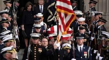 PENGHORMATAN TERAKHIR: Bush dan isterinya Laura menyertai pengawal kehormat yang mengusung keranda bapanya, H.W. Bush,            ke kereta mayat yang menunggu di luar selepas upacara pengebumian rasmi di Katedral Nasional di Washington kelmarin. — Gambar AFP