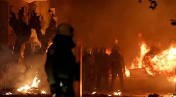 PROTES BERAPI: Polis rusuhan dilihat berdiri di antara api-api sewaktu tunjuk perasaan bagi      memperingati Grigoropoulos, di Athens kelmarin. — Gambar Reuters