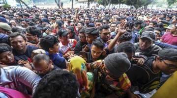 'LAUTAN MANUSIA': Antara gelagat penyokong pasukan Malaysia ketika berasak bagi mendapatkan tiket menjelang Perlawanan Akhir Piala AFF Suzuki 2018 di Stadium Bukit Jalil, semalam. — Gambar Bernama
