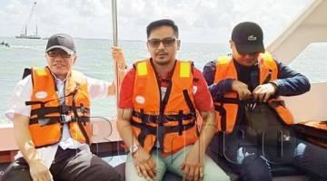 LIEW (kiri) bersama Setiausaha Sulit Mohd Hanapiah Sahih Haji Mantoi menaiki bot ke Pulau Timbang, Batu Sapi.