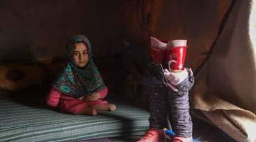 'KAKI' BAHARU: Maya bergambar di sisi kaki prostetiknya yang dihiasi dengan bendera Turki di dalam sebuah khemah di kem 'Orang Pelarian Dalaman' (IDP) di Serjilla, barat laut Syria, bersebelahan pintu sempadan Bab al-Hawa dengan Turki, kelmarin. — Gambar AFP