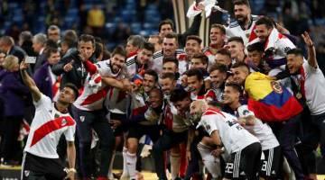 DETIK BERSEJARAH: Para pemain River Plate meraikan kejayaan mereka menjuarai Copa Libertadoresselepas tamat perlawanan di Santiago Bernabeu, Madrid kelmarin. — Gambar Reuters