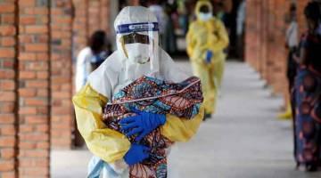 MANGSA EBOLA: Seorang pekerja kesihatan membawa seorang bayi yang disyaki           dijangkiti virus Ebola di sebuah hospital di Oicha, Congo pada 6 Disember lepas. — Gambar Reuters