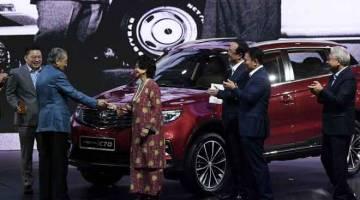 PELANCARAN: Tun Dr Mahathir menyerahkan kunci kereta kepada isterinya Tun Dr Siti Hasmah ketika melancarkan Proton SUV X70 di Pusat Konvensyen Kuala Lumpur, malam kelmarin. — Gambar Bernama