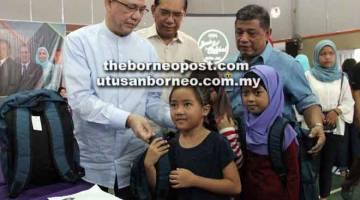 RINGANKAN BEBAN: Fadillah (kiri) menyerahkan bantuan beg sekolah termasuk pakaian dan kelengkapan persekolahan kepada pelajar yang memerlukan dalam kawasan Petra Jaya di Dewan Kampung Malaysia Jaya di Kuching semalam.