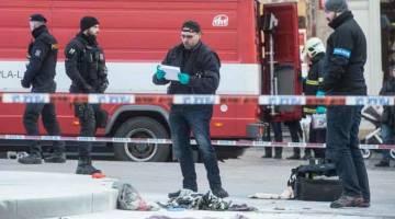 MASIH DALAM SIASATAN: Pegawai polis menjalankan siasatan di lokasi di  mana seorang lelaki membakar diri kelmarin di Prague. — Gambar AFP