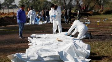 RENTUNG: Juruteknik forensik menanda mayat di tempat kejadian dalam kawasan perbandaran Tlahuelilpan di negeri Hidalgo, kelmarin. — Gambar Reuters