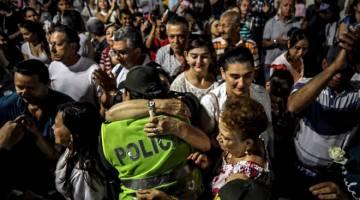 SOKONGAN: Seorang anggota polis wanita dipeluk seorang wanita warga emas semasa upacara peringatan mangsa serangan bom kereta di Bogota, di Itagui dekat Medellin, bahagian Antioquia kelmarin. — Gambar AFP