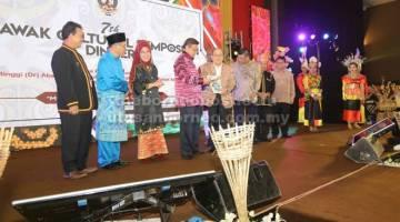 RESOLUSYEN: Abang Johari (empat kiba) nerima bup rintai resolusyen Simposium Budaya Sarawak Ketujuh 2018 ari Uggah (lima kiba) seraya dikemataka  bala  temuai ti di pebasa ke bukai.