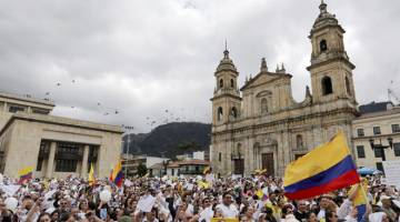BANTAH KEGANASAN: Ribuan rakyat Colombia menyertai perarakan membantah keganasan ekoran serangan bom kereta ke atas sebuah akademi polis yang membunuh 20 kadet dan seorang penyerang di Bogota, Colombia pada Ahad. — Gambar Reuters