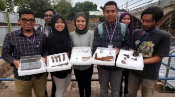 PENEMUAN BERHARGA: Siswazah Pusat Penyelidikan Arkeologi Global Universiti Sains Malaysia menunjukkan artifak zaman penjajahan British yang ditemui. — Gambar Bernama
