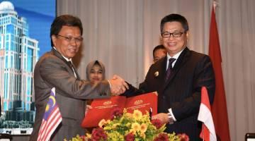 KERJASAMA: Mohd Shafie Dr Irianto (kanan) bertukar dokumen risalah yang dimeterai pada perjumpaan ahli Jawatankuasa Kerja Sosial-Ekonomi Malaysia-Indonesia (SOSEK MALINDO) 2019 antara Sabah dan Kalimantan Utara semalam. — Gambar Bernama