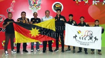 Ahmad Rodzli (empat kiri) bersama Ali (tiga kiri), jurulatih dan petinju semasa majlis penyerahan bendera di lobi Stadium Sarawak, Petra Jaya hari ini.