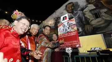 SENI: Abdul Karim menandatangani poster sebagai simbolik perasmian Seni Mural Jalanan yang pertama dilancarkan di Lebuh India sempena sambutan Cap Goh Meh, malam kelmarin. Turut kelihatan Wee (kanan), Dr Sim (kiri) dan Abang Abdul Wahap.