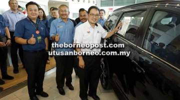 PASTIKAN ADA LABEL: Chong melekatkan label ASEAN NCAP pada cermin kenderaan Perodua                 Aruz pada Majlis Penyempurnaan Pelabelan di Pusat Pameran Perodua di Jalan Sherip Masahor                di Kuching, semalam. Turut kelihatan Desmond (kiri) dan Rostam. — Gambar Chimon Upon