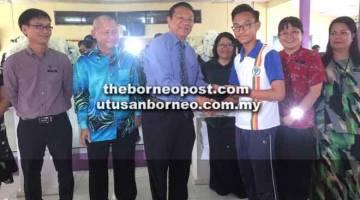 RINGAN BEBAN: Dr Teo menyampaikan kupon kepada salah seorang pelajar SMKDP disaksikan guru dan ahli PIBG semasa lawatan semalam.